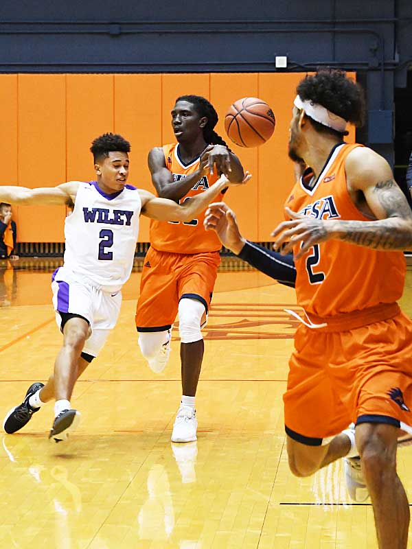 UTSA's Keaton Wallace (center) passes the ball up to Jhivvan Jackson. UTSA beat Wiley College 90-68 on Friday in the Roadrunners' first home game of the 2019-20 men's basketball season. - photo by Joe Alexander