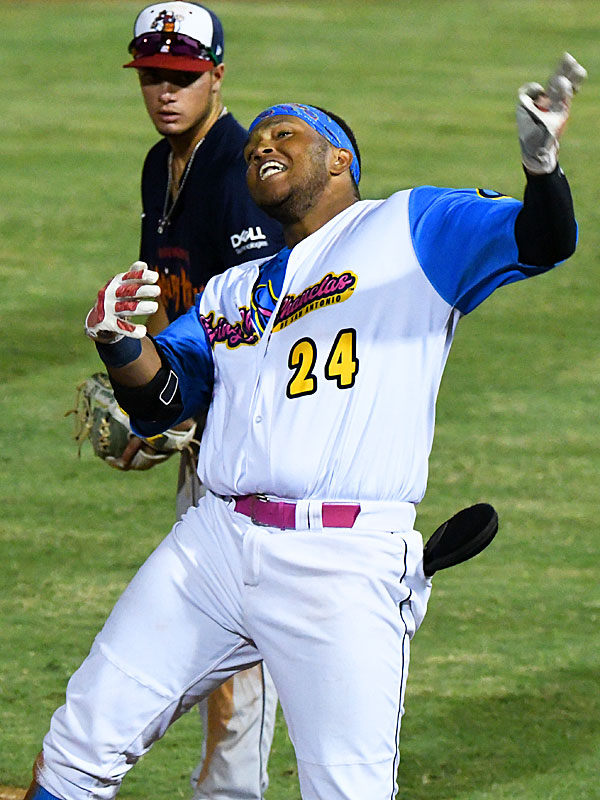 The Flying Chanclas' Lee Thomas celebrates after his RBI triple off the wall in center in the bottom of the eighth inning. - photo by Joe Alexander