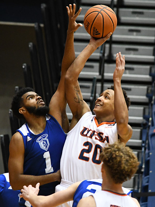 OLLU's Jordan Embry (1) contests a shot by UTSA's Eric Parrish as UTSA beat Our Lady of the Lake 102-70 on Sunday, Dec. 20, 2020, at the UTSA Convocation Center. - photo by Joe Alexander
