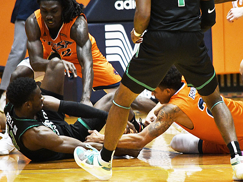 UTSA's Keaton Wallace (top left) and Eric Parrish (bottom right) wrestle with North Texas' Thomas Bell (bottom left) for a loose ball on Saturday at the Convocation Center. - photo by Joe Alexander